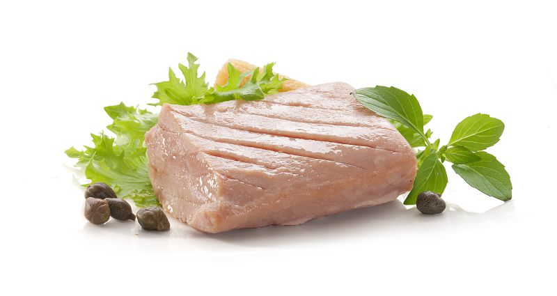 Piece of tuna fillet with fresh green lettuce, basil and mini corn